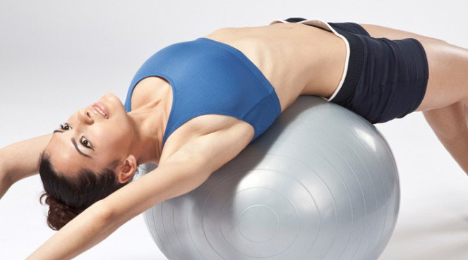 Woman on a stability ball getting a flat belly fix workout