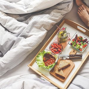 A woman eating in bed because her sleep schedule is messed up