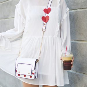 A woman in a white dress with a white handbag