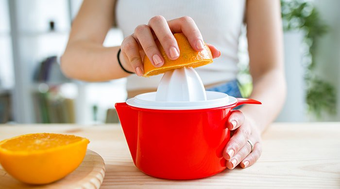 A woman squeezing orange juice for her juice cleanse