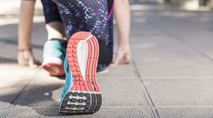 A woman in running shoes using a 10K training plan