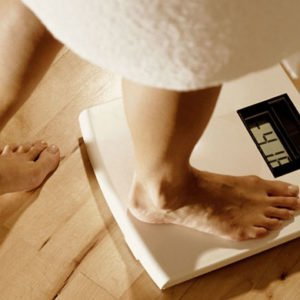 A woman stepping onto a scale after trying a paleo diet