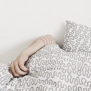 A woman hiding under the covers because she's having whack dreams