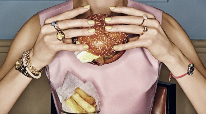 Woman holding a burger which is one thing that won't up your metabolism