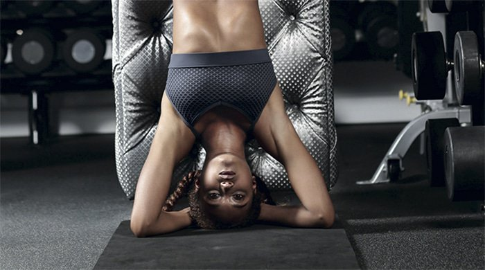 Woman doing a headstand at the gym
