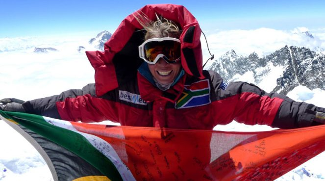 Lee den Hond, holding the South African flag atop Mount Everest.