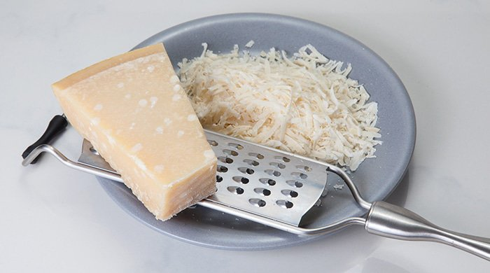 A bowl full of grated cheese made from dairy