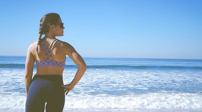 A woman in her workout gear sanding on the beach because it is one of her rest days
