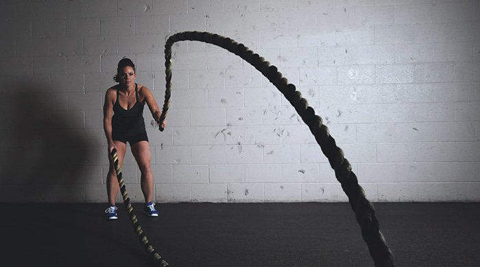 A woman using a rope to workout