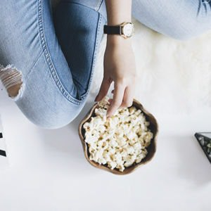 a woman eating popcorn in bed