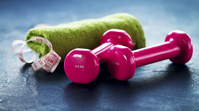 a pair of dumbbells and a tape measure to measure belly fat