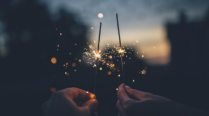 Two people holding sparklers to represent partner orgasm benefits