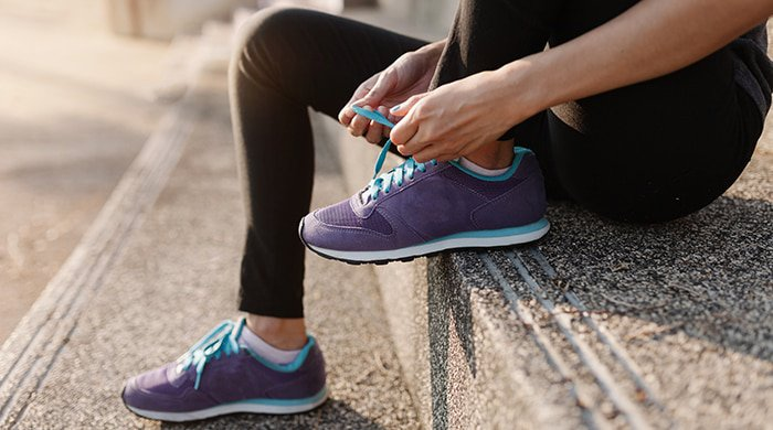 A woman tying her shoe laces before her walking workouts