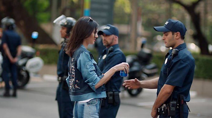 kendall jenner handing a police officer a can of pepsi