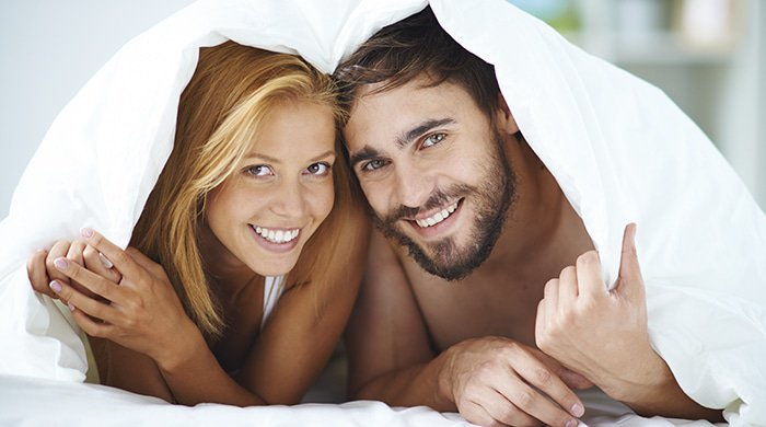 a couple in bed who've just tried a popular sex position