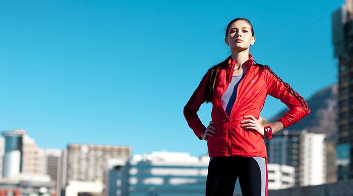 A woman in workout gear outside despite having allergies