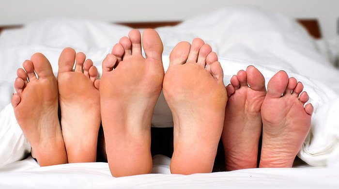 three people in bed embracing open relationships