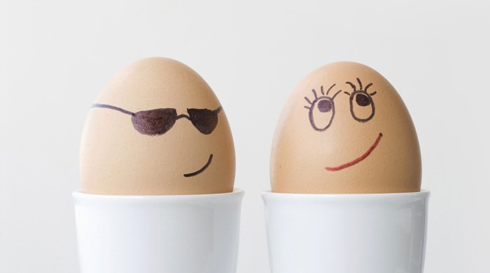 two eggs with drawn on faces that represent two people having an affair