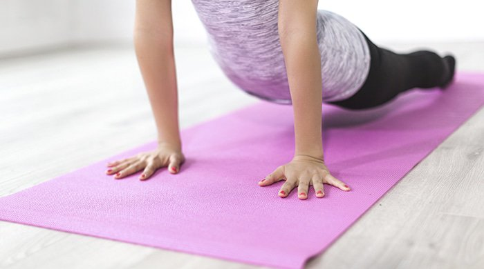 A woman on a pink mat doing yoga