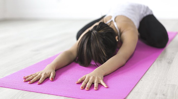 a woman doing yoga on a pink mat