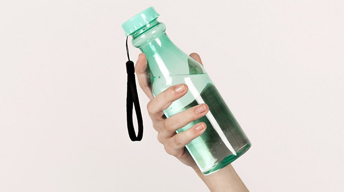 A close-up of a woman holding a water bottle to symbolise water weight