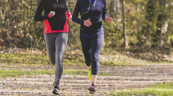 Two women running on a dirt path