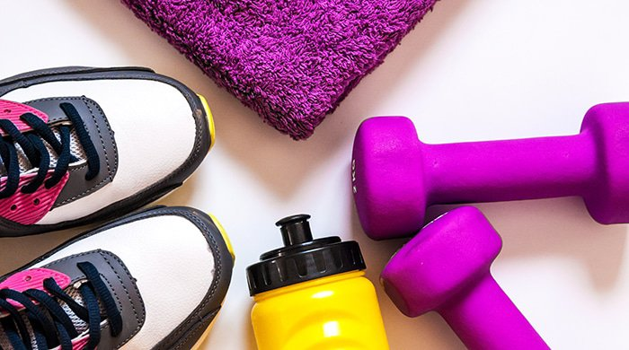 Sneakers, towel, water bottle and dumbbells are the equipment you need for workout programmes