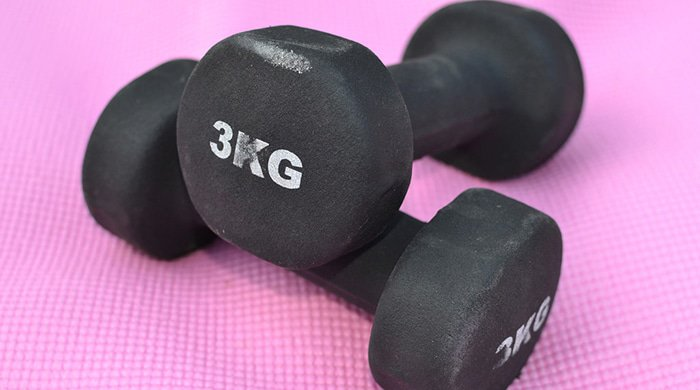 dumbbells on a pink mat for a workout