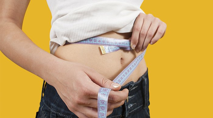 woman measuring centimetres to determine body fat