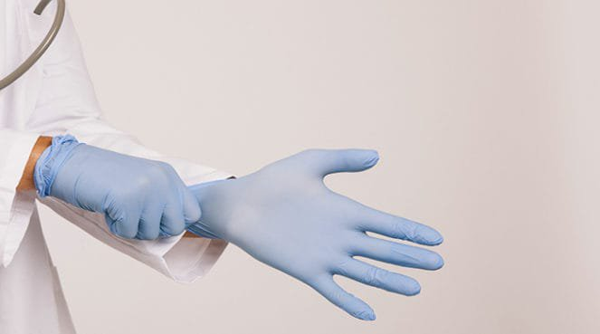 A doctor putting on gloves about to perform an abortion