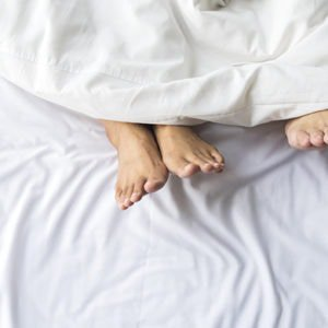 A couple in bed who have chosen the best time of day to have sex