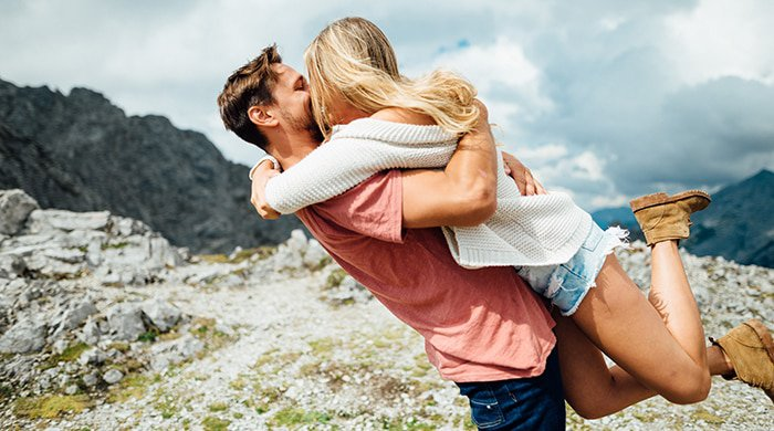A couple hugging on top of a cliff to symbolise first love