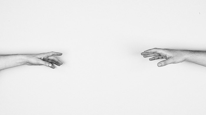 Black and white image of two people reaching out to each other to illustrate how this real life couple rediscovered their intimacy after cancer