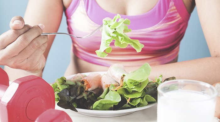 a woman in a pink sports bra eating a restrictive diet