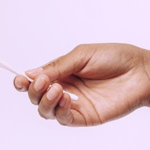 A woman holding cotton swabs for earwax removal