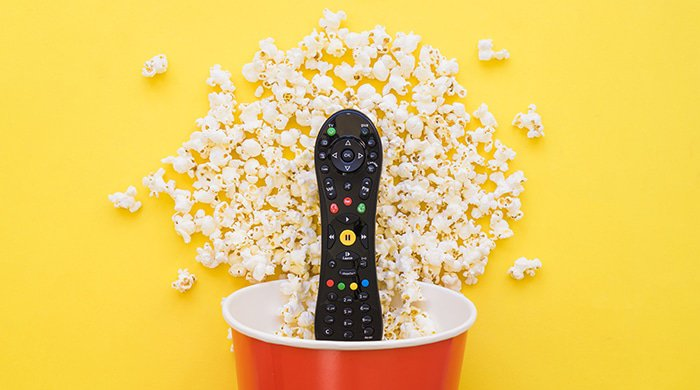 a remote, in a popcorn bucket with popcorn to represent the making of a sex tape