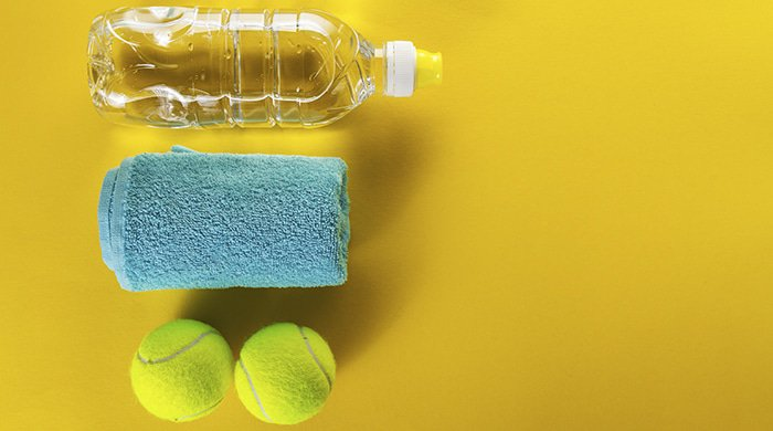 water bottle, towel and tennis balls on a yellow background to represent a workout