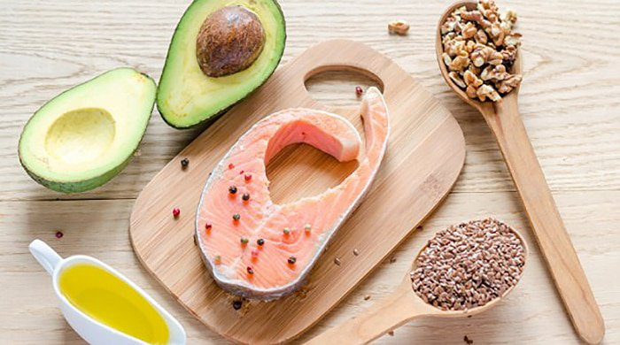 High-fat foods on a wooden board to represent eating fat