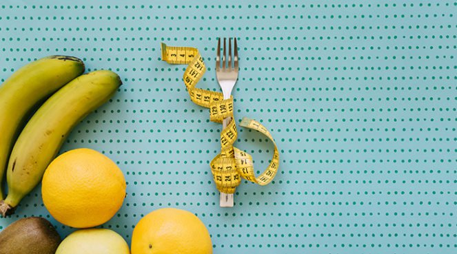 A measuring tape around a fork on a blue background to represent how one can track weight loss progress