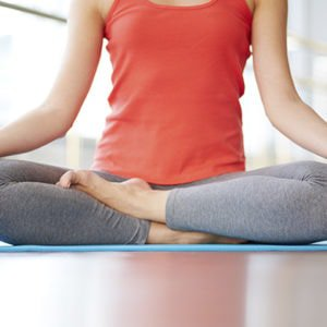 a woman's legs in lotus position while she does yoga