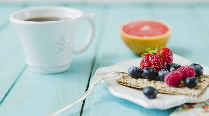 A cup of coffee, grapefruit and berries to represent healthy meals