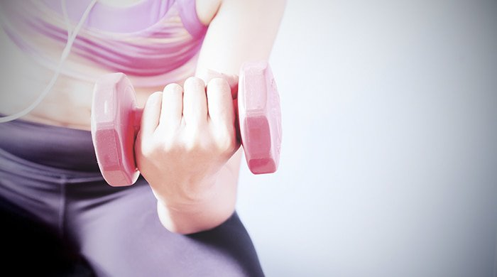 A close-up of a woman with a pink dumbbell for toned arms