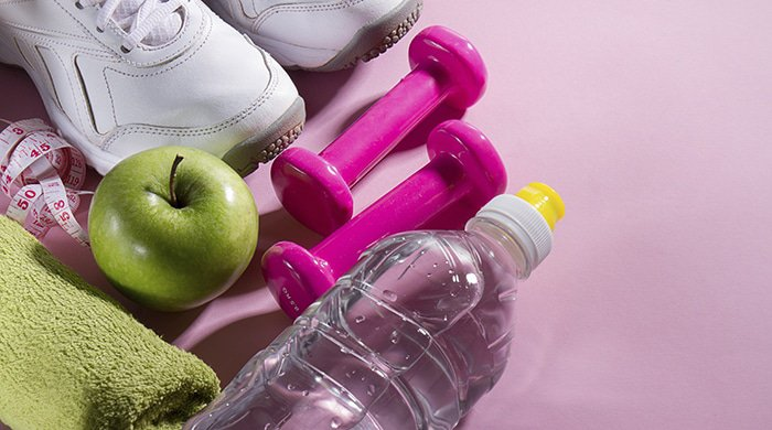 fitness flat lay on pink background to represent a weight loss mistake you could be making