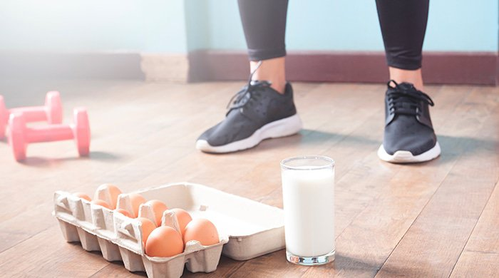 A woman in workout shoes standing next to dumbbells, eggs and milk to represent the link between workouts and a weight-loss plan