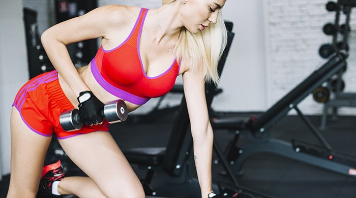 A woman lifting a dumbbell to get rid of arm fat