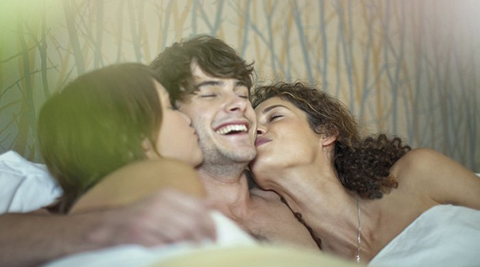 A man in bed with two women because he found out his partner was bisexual and wants to have a threesome