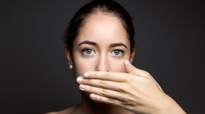 A woman with her hand in front of her mouth to stop herself from saying sorry