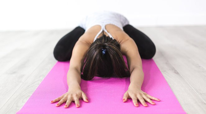 A woman on a yoga mat to represent yogi gifts for the festive break