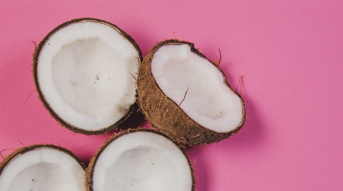 Coconuts and coconut oil on a pink background