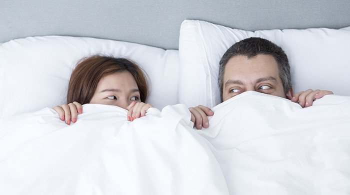 a couple in bed having a hard time during their first year of marriage